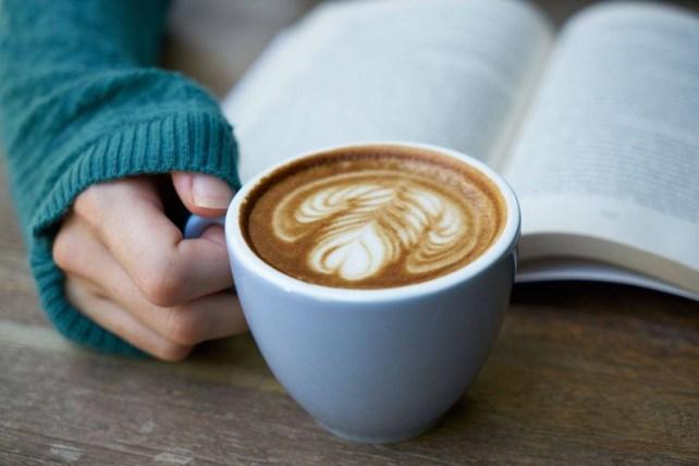 Menneske som leser med kaffekopp i hånden