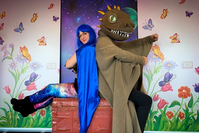 Jente med blått hår og kappe og levende drage