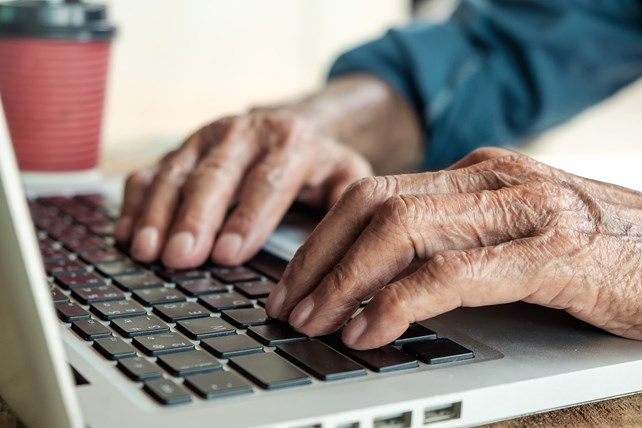 Eldre persons hender på tastaturet på en laptop