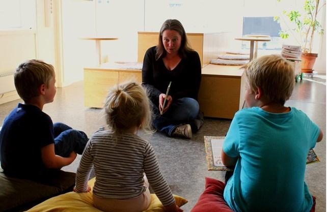 Bibliotekar leser for tre barn, to gutter og en jente