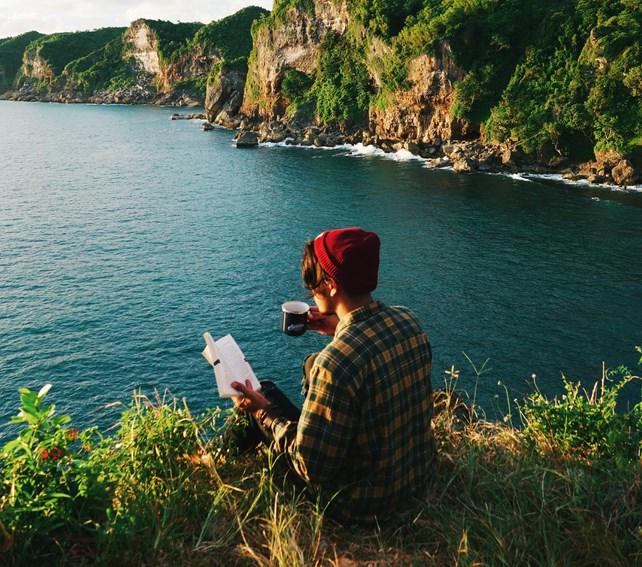 Person som leser bok ved havet.